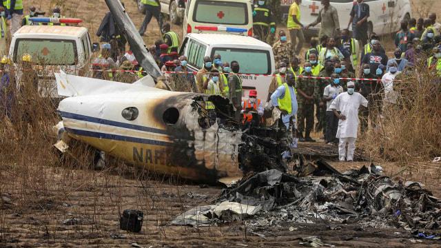 Tim penyelamat dan orang-orang berkumpul di dekat puing-puing pesawat angkatan udara Nigeria, yang menurut menteri penerbangan jatuh saat mendekati landasan pacu bandara Abuja, di Abuja, Nigeria, Minggu (21/2/2021). Foto: Afolabi Sotunde/Reuters.
