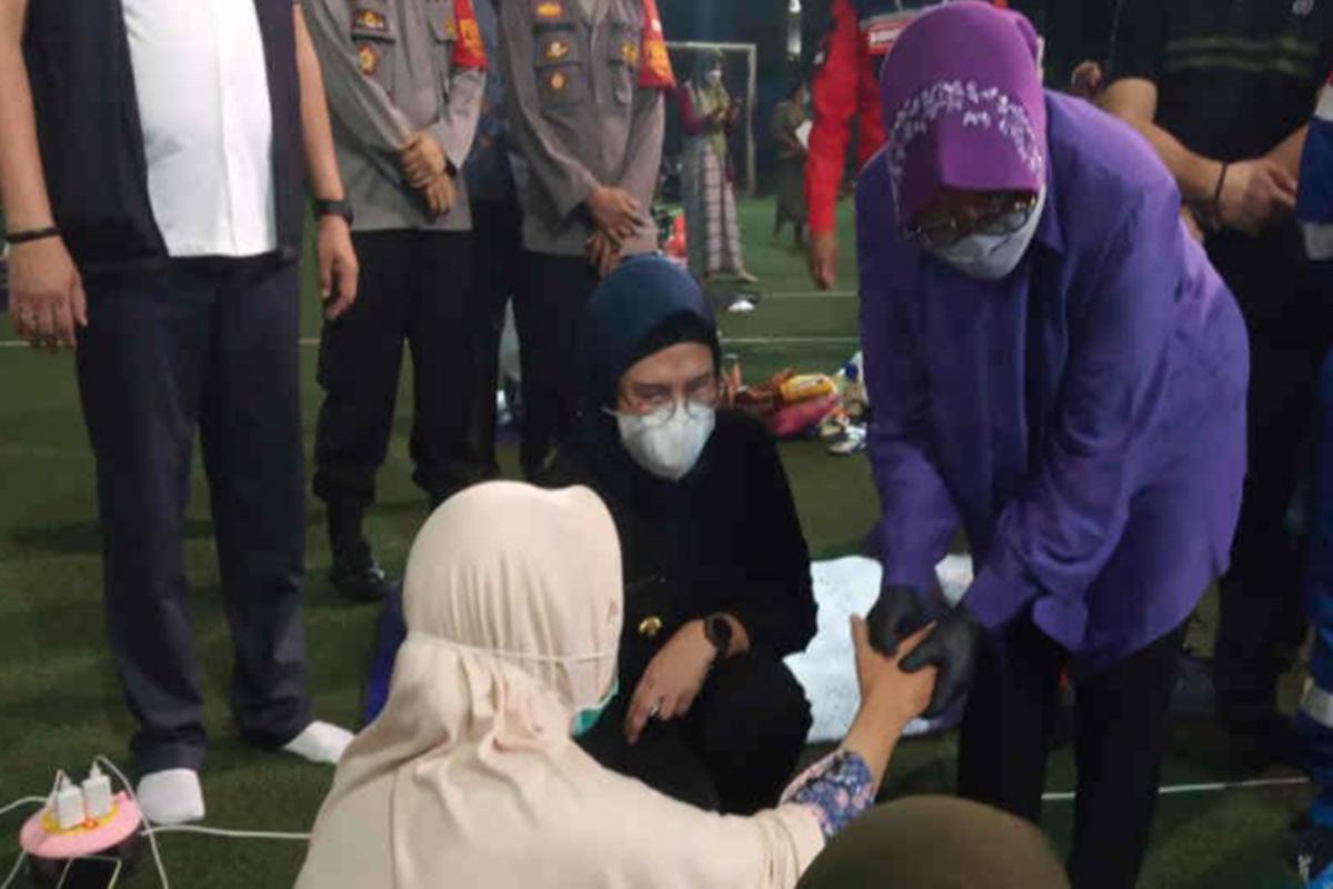 Tri Rismaharini mengecek kondisi pengungsi korban kebakaran kilang Pertamina Balongan, Indramayu. Dia sempat memijat warga dan matanya berkaca-kaca (foto: Antara)