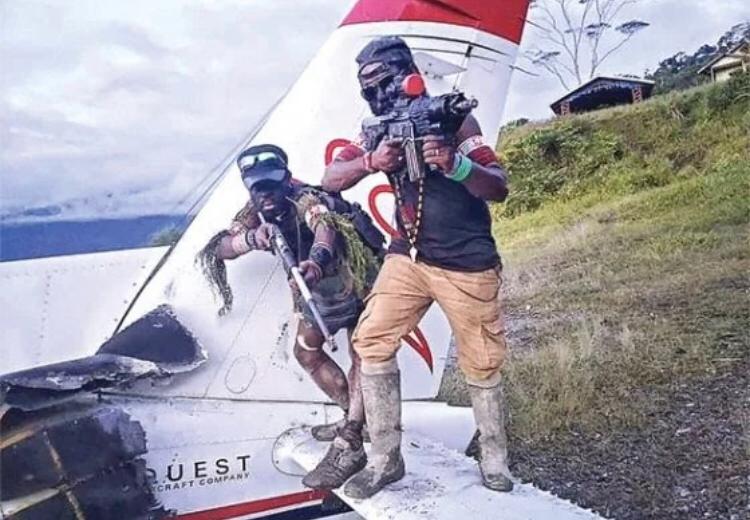 Dua orang yang diduga anggota KKB naik ke puing pesawat sambil menunjukkan senjatanya. (SEBBY SEMBOM FOR CEPOS)