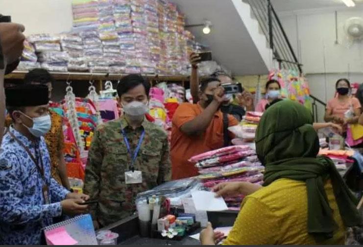 Wali Kota Solo Gibran Rakabuming Raka (dua dari kiri) saat mengembalikan uang pungli dan meminta maaf kepada pemilik toko di Kelurahan Gajahan Pasar Kliwon Solo, Minggu (0205/2021) (ANTARA/Bambang Dwi Marwoto)