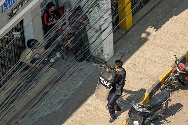 Polisi Myanmar menodongkan senjatanya ke arah demonstran dari jarak dekat. Foto/Bangkok Post