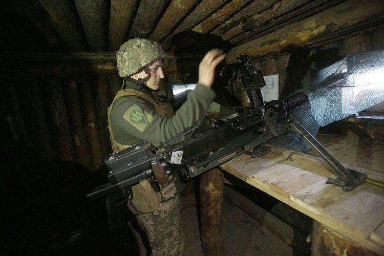 Tentara Ukraina mengisi ulang senapan mesin di pos garis depannya yang berhadapan dengan separatis dukungan Rusia dekat Schastya, wilayah Lugansk, 16 April 2021.(STR/AFP)