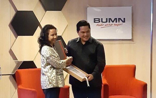 Menteri BUMN periode 2014-2019 Rini Soemarno menyerahkan buku laporan lima tahunan Kementerian BUMN kepada Menteri BUMN Erick Thohir. Foto: ANTARA/Aji Cakti