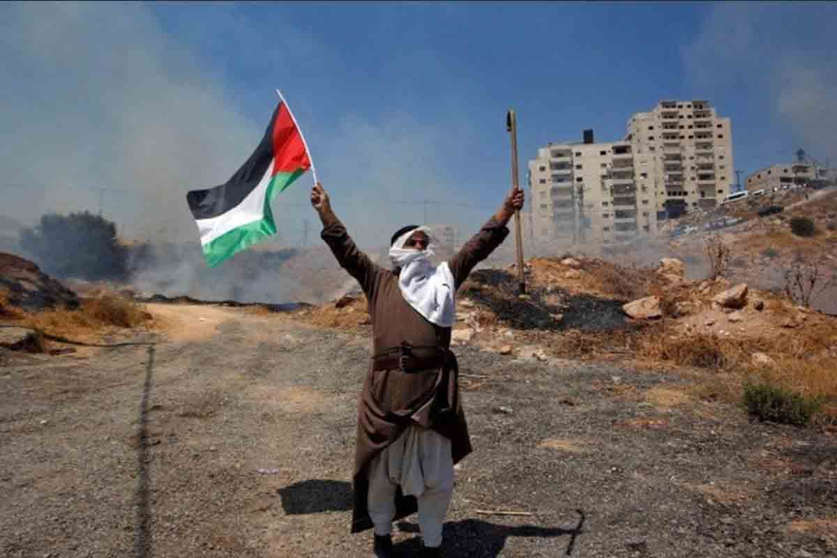 Seorang pengunjuk rasa membawa bendera Palestina saat melakukan protes atas penghancuran rumah warga Palestina oleh Israel di desa Sur Baher. Foto: Antara/Reuters/Mussa Issa Q.
