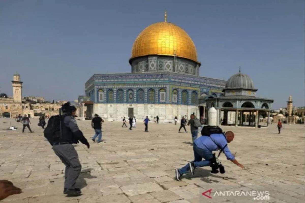 Seorang kameramen terjatuh saat seorang polisi Israel mengejarnya saat terjadi bentrokan dengan warga Palestina di halaman Masjid Al Aqsa. (FOTO: REUTERS)