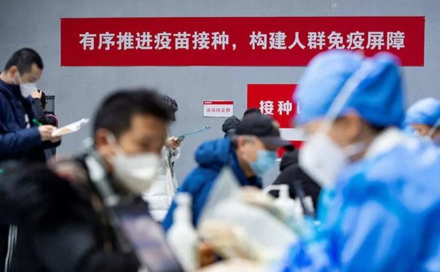 Warga memberikan formulir untuk menerima vaksin penyakit virus corona di tempat vaksinasi sementara di distrik Chaoyang, Beijing, China. ANTARA FOTO/cnsphoto via REUTERS/rwa/cfo/am.