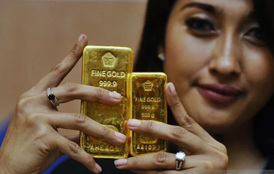 Seorang petugas memperlihatkan emas batangan produksi PT Antam di Jakarta. ANTARA FOTO/Wahyu Putro A/ss/ama.