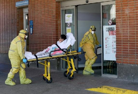 Petugas medis tiba bersama seorang pasien di Rumah Sakit Severo Ochoa di tengah wabah virus corona (COVID-19) di Leganes, Spanyol, Kamis (26/3). (REUTERS/SUSANA VERA)