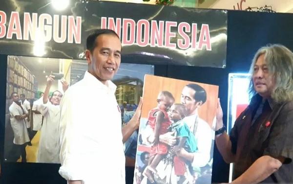 "Presiden Joko Widodo menerima foto dari kurator Oscar Motuloh usai mengunjungi Pameran Foto ""Membangun Indonesia"" di Mall Neo Soho, Central Park, Jakarta pada Selasa (12/11/2019). (ANTARA/Bayu Prasetyo)"