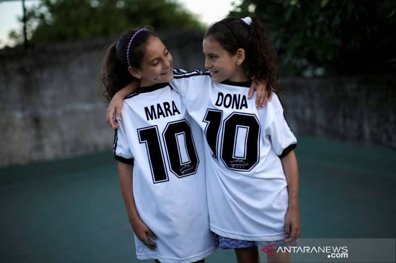 Mara dan Dona, putri kembar Walter Gaston Rotundo, berpose di rumah mereka, di Buenos Aires, Argentina, 27 November 2020. REUTERS / Ueslei Marcelino