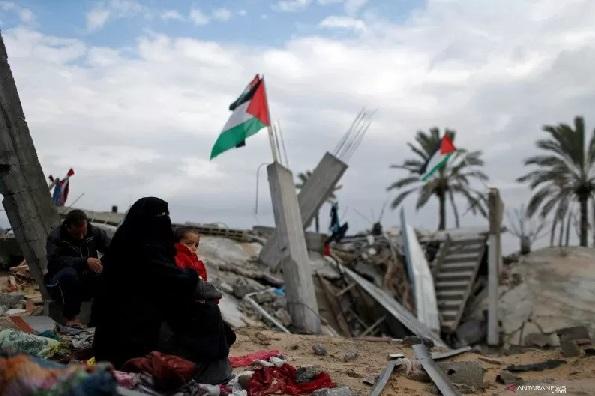 Anggota keluarga Palestina duduk di lokasi rumah mereka yang hancur, pada sebuah hari musim dingin di selatan Jalur Gaza, Senin (13/1/2020). REUTERS/Mohammed Salem/wsj/cfo (REUTERS/MOHAMMED SALEM)