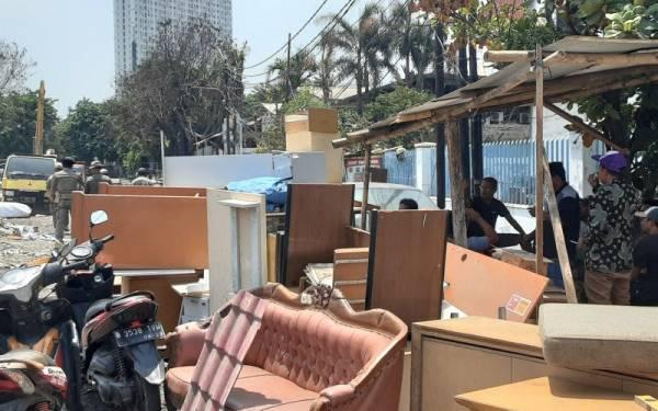 Warga korban penggusuran di Jalan Sunter Agung Perkasa VIII, Kecamatan Tanjung Priok, Jakarta Utara masih bertahan di puing-puing bangunan bekas rumah mereka, Sabtu (16/11). Foto: ANTARA/Fauzi Lamboka