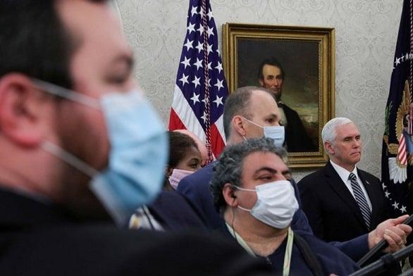 Wakil Presiden Amerika Serikat Mike Pence berdiri di antara pengarah suara televisi, wartawan radio, dan awak media lain, yang semuanya menggunakan masker sebagai pencegahan terhadap virus corona (COVID-19), saat mendengarkan Donald Trump memberikan perny