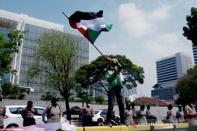 Seorang demonstran mengibarkan bendera Palestina saat berunjuk rasa di depan Kedutaan Besar Amerika Serikat, di Jakarta, Selasa (18/5/2021). (ANTARA/Genta Tenri Mawangi)