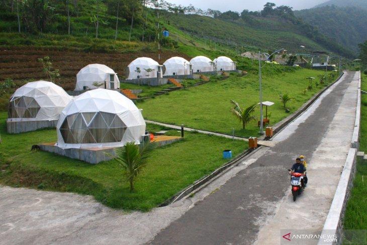 Wisatawan melintas di samping bangunan penginapan tahan gempa di Lembah Indah Resort, Malang, Jawa Timur, Selasa (8/6/2021). Antara Jatim/Ari Bowo Sucipto/zk
