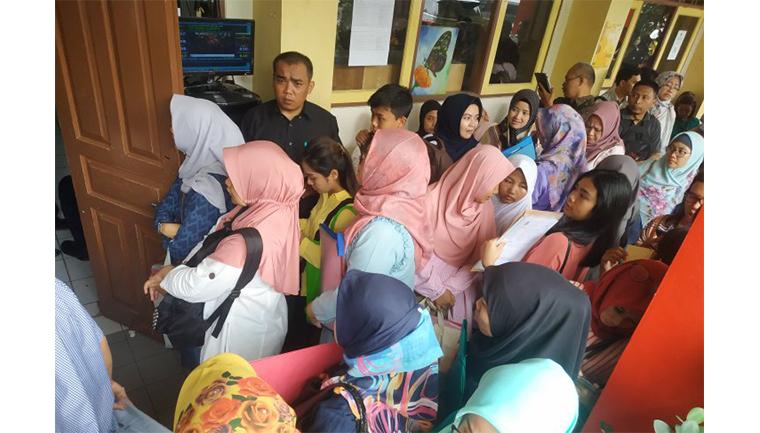 Orangtua siswa mengantre saat Pendaftaran Penerimaan Peserta Didik Baru (PPDB) Jalur zonasi di SMP 115, Jakarta, Senin (24/6/2019). (Sumber foto: ANTARA FOTO/Muhammad Adimaja)