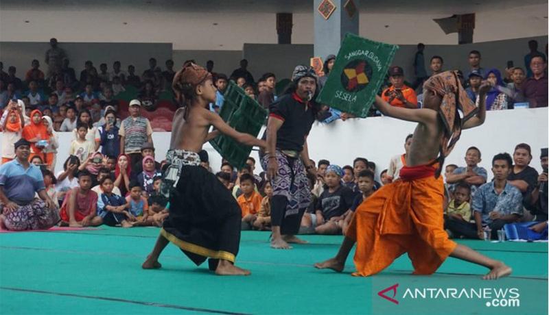 Dua orang remaja adu pukul menggunakan rotan sambil membawa tameng terbuat dari kulit sapi (peresean) dalam pagelaran peresean dan pepaosan di gedung budaya Narmada, Kabupaten Lombok Barat, NTB, Senin (22/7). (Sumber foto: ANTARA/Awaludin)