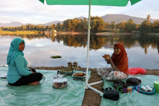 Dua orang wisatawan sedang menikmati kuliner di tepi Danau Perintis, Bone Bolango.