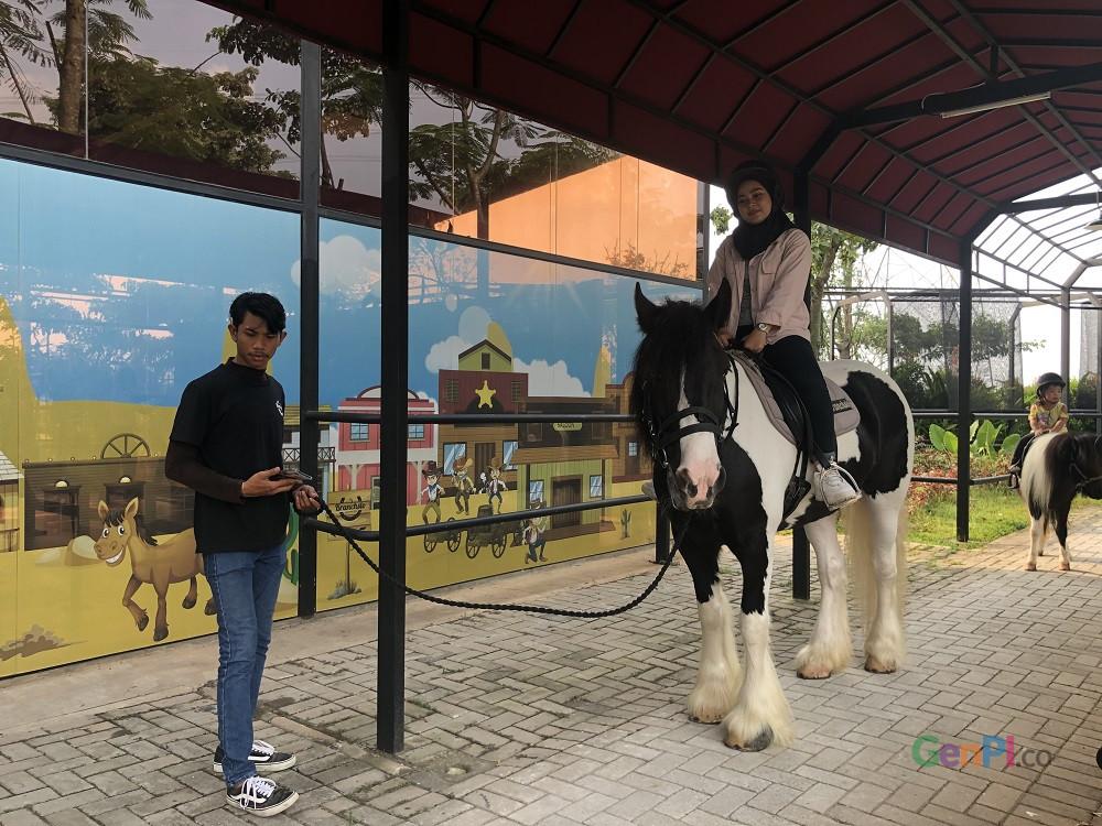 Seorang pengunjung Branchto Equstrian Park sedang mencoba menunggang kuda.