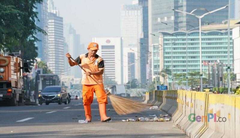 Suyato, petugas pasukan orange sedang membersihkan sampah sisa demo di depan Gedung Bawaslu, Jakarta. Foto: Ririn