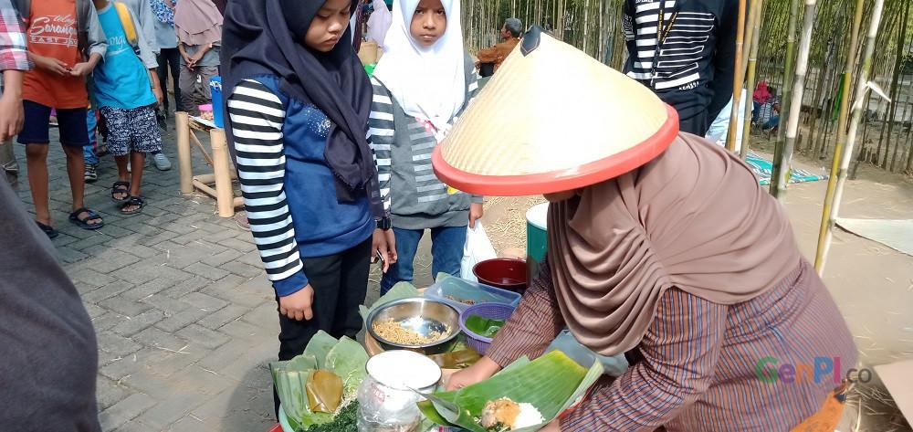 Seorang pedagang tenhah melayani pengunjung di Pasar Jadul Ahad Legi, Minggu (30/6).